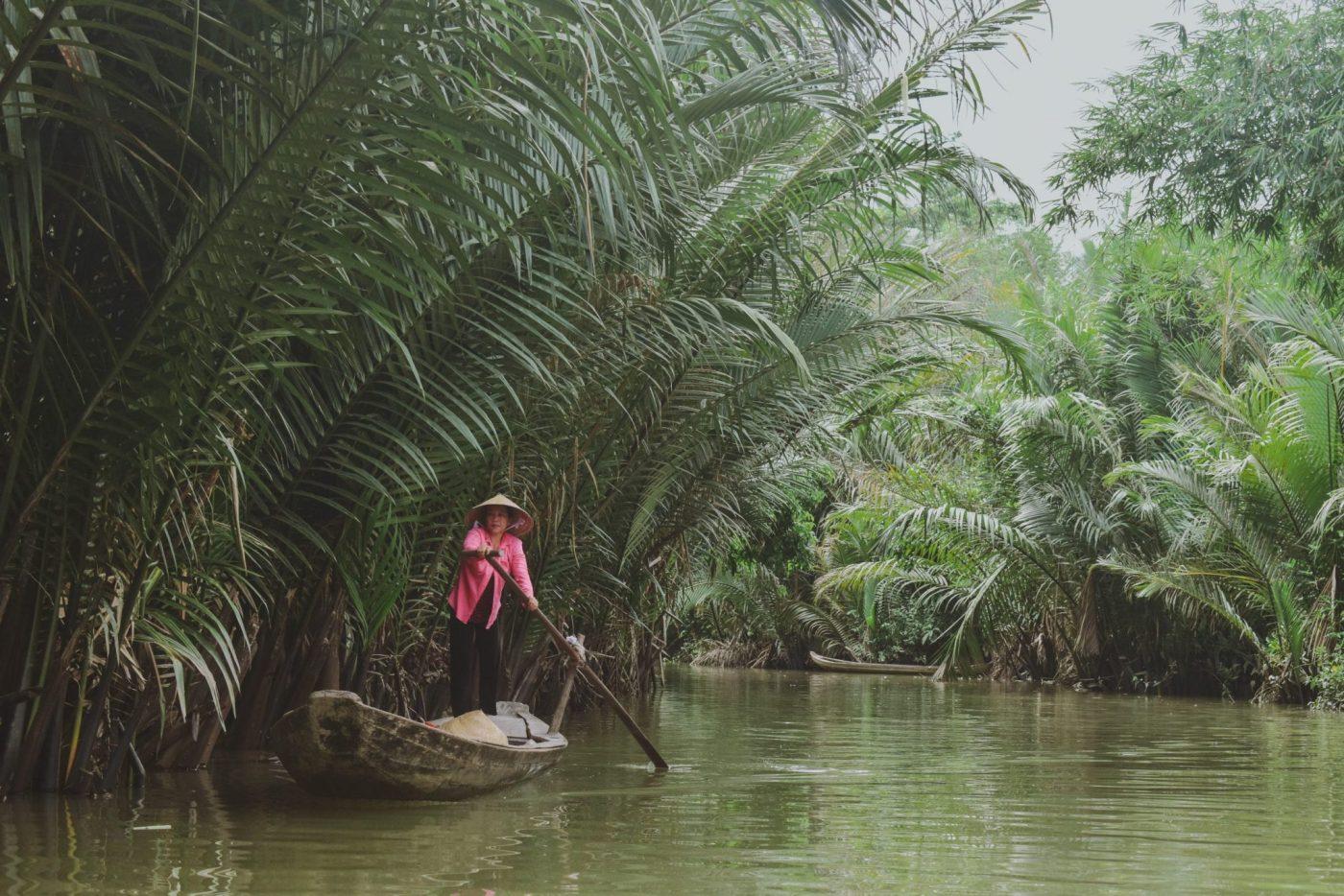 A woman rowing down a tropical river, Vietnam