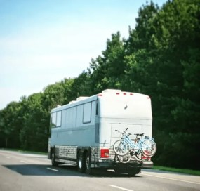 Customized Class A Motorhome with a bike rack driving on the highway