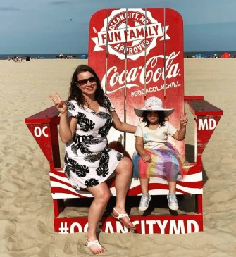 Melanie and Lea sitting on the red photo op chair in chair at the Ocean City Boardwalk