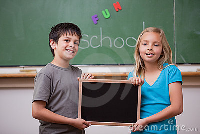 Stock Images: Smiling pupils holding a school slate. Image: 22692474