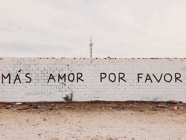 """More love please"" phrase written on a wall"