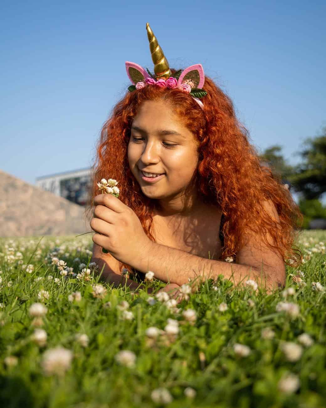 photo of a woman wearing unicorn headband looking at flowers