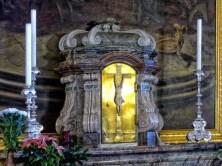 Kreuz auf Altar mit Kerzen