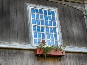 Großes Fenster mit Blumen Holzfassade