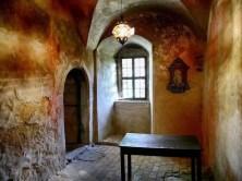 Kleiner Raum mit Lampe und Tisch Gemäuer