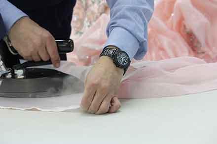 何重にもなったスカート部分の内側を1枚1枚丁寧にアイロンをかける