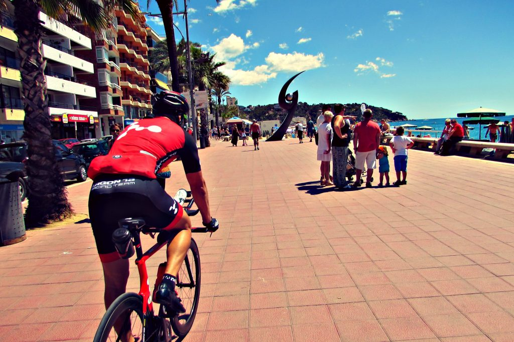 Cycling along the beach at Lloret de Mar, Costa Brava, Spain