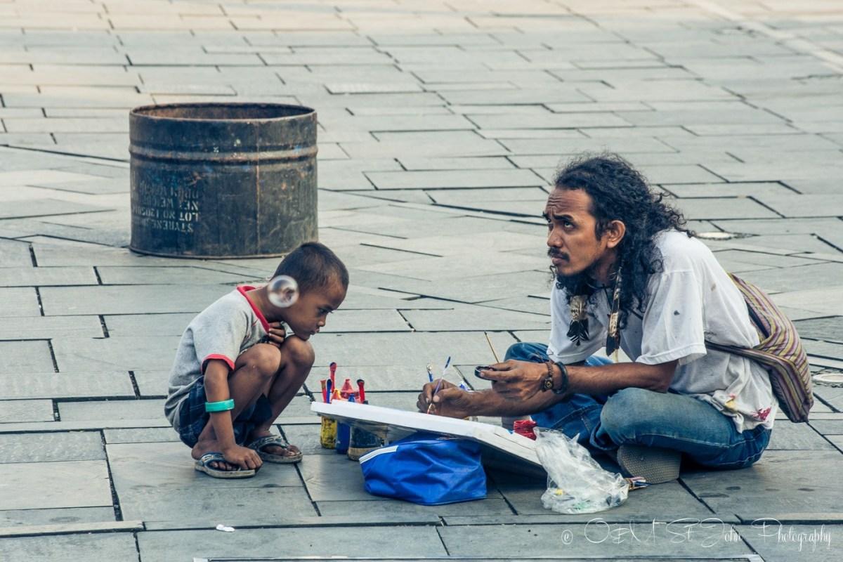 A boy watching a man paint in Taman Fatahilah, Old Jakarta