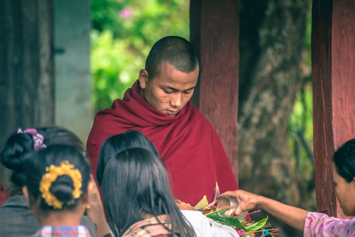 Burmese monk collecting offerings from the local people outside of the monastery in Myanmar.