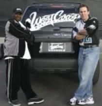"Craig Steichen, VP of Marketing for Super Concepts, and Q of West Coast Customs (MTV's ""Pimp My Ride"") stand next to a customized 2005 Ford Escape SUV. (Photo from Ford; February 2005)"