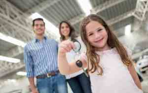 Family buying a car and girl holding the keys