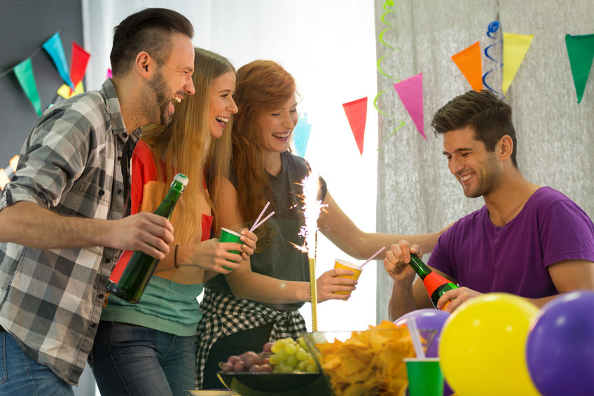 Students having home party, man holding bottle of champagne