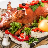 Decorated and roast suckling pig on a table on banquet at restaurant