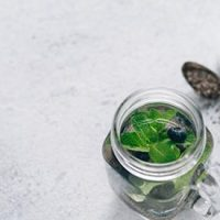 View from above chia water in mason jar with mint and blueberry on gray cement background. Chia infused detox water with berries. Copy space for text. Healthy eating, drinks, diet, detox concept