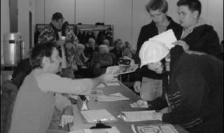 Légende : Pendant l'assemblée publique, le 5 décembre dernier au Centre Durocher. Une femme et deux jeunes hommes devant une table de vote ou d'information. Un bénévole moustachu leur tend un document. Derrière des citoyens sont assis et un autre est debout avec un café.