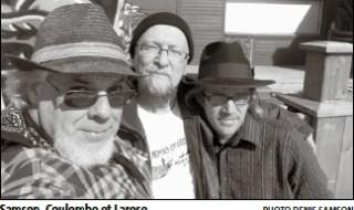 Photo de 3 hommes se tenant épaules à épaules chaleureusement: le premier barbe blanche, lunettes, chapeau, foulard, regarde la caméra; le 2e porte une tuque, barbe blanche, lunettes, T-Shirt; le 3e plus petit avec chapeau noir, lunettes, cheveux qui dépassent sur les côtés.
