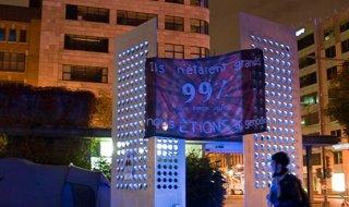 Photo : structure de métal au milieu de la place où était Occupons Québec. Bannière: Ils n'étaient grands 99 % que parce que nous étions à genoux.
