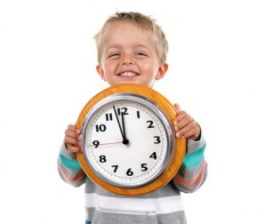 Smiling nursery school child holding a clock