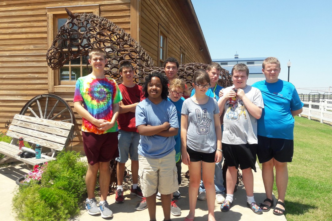 A group of Camp Tumbleweed campers pose for a group picture at Express Ranch.