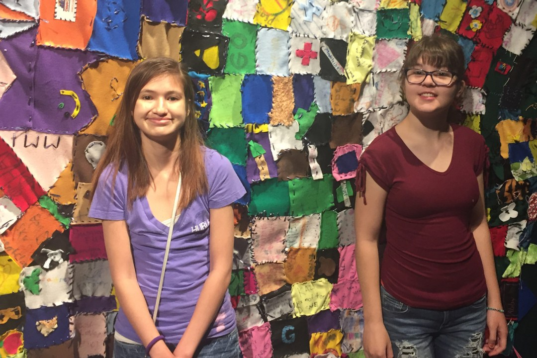 Two campers with Camp Tumbleweed pose for a picture in front of a quilt wall.