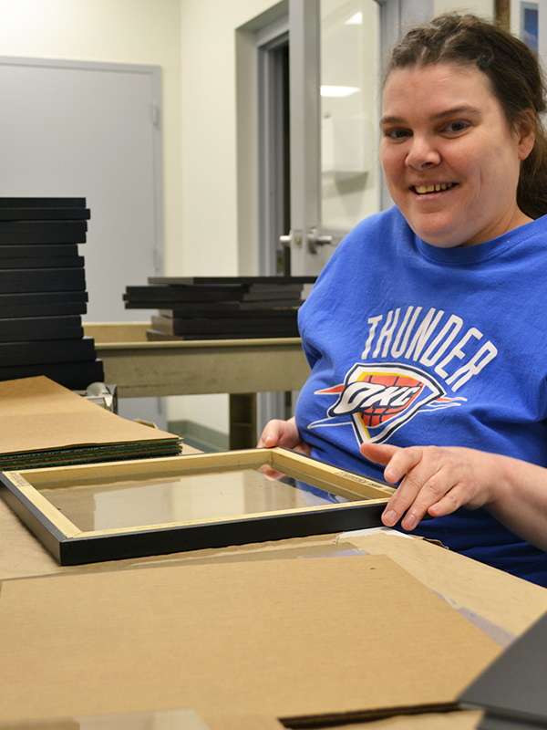 Julie smiling while assembling a picture frame at Wyman Frame.