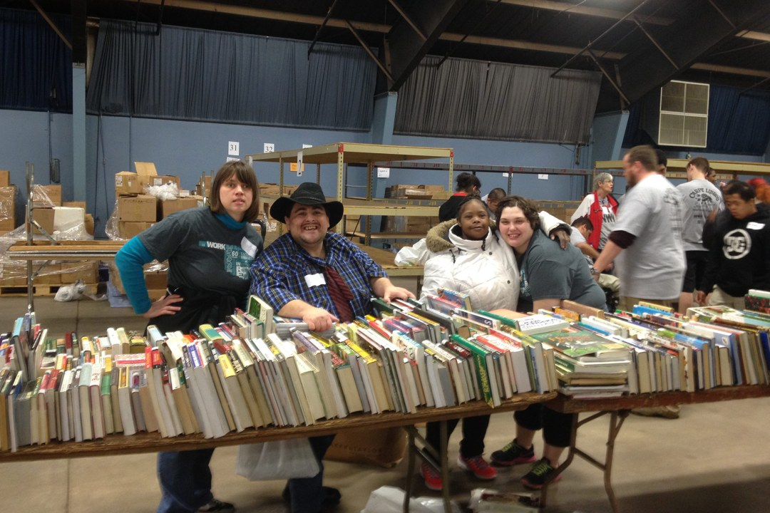 A group of individuals pose for a picture while volunteering at the Friends of the Library Booksale.