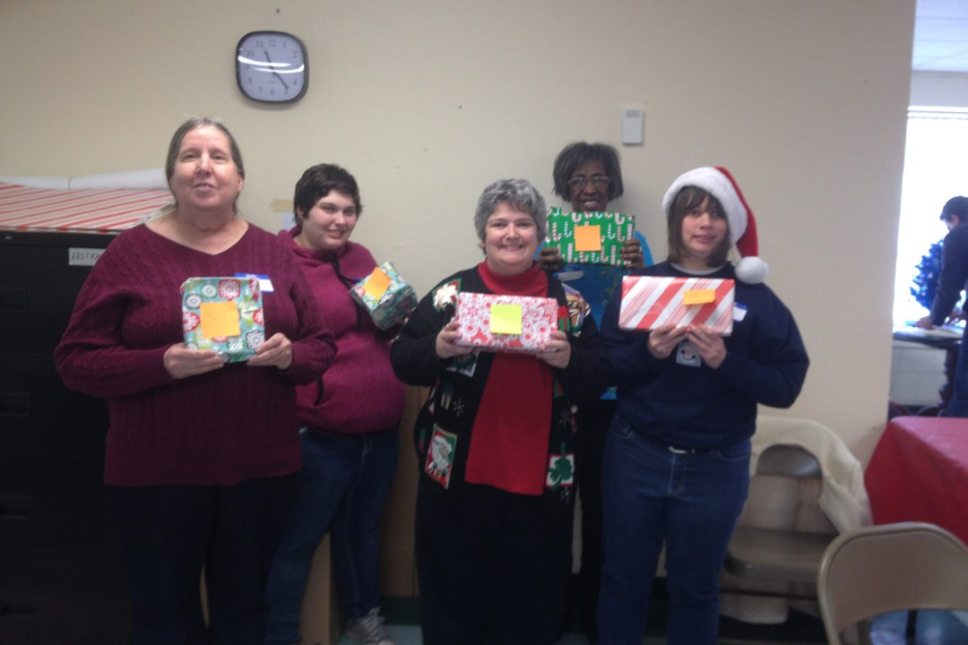 Five individuals with DRTC's Mobile Workforce hold up wrapped gifts they wrapped while volunteering at Salvation Army.