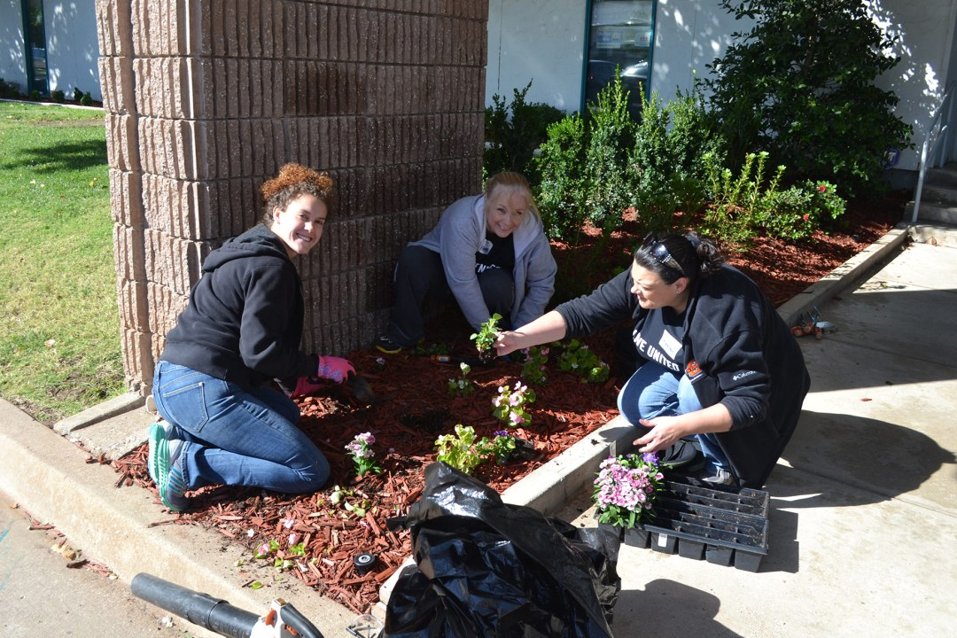 Three volunteers with OSU-OKC plant flowers at DRTC.