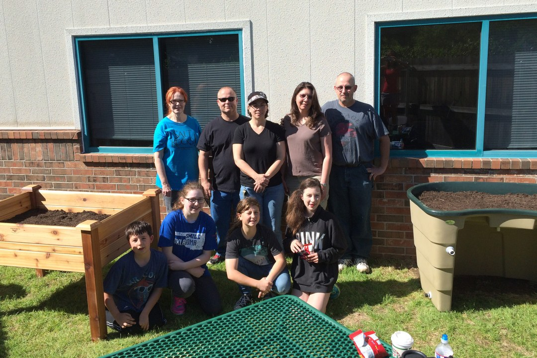 Volunteers with a Girl Scout troop take a group photo after assembling raised flower beds at DRTC.