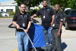 Three custodial crew members with their cleaning equipment.