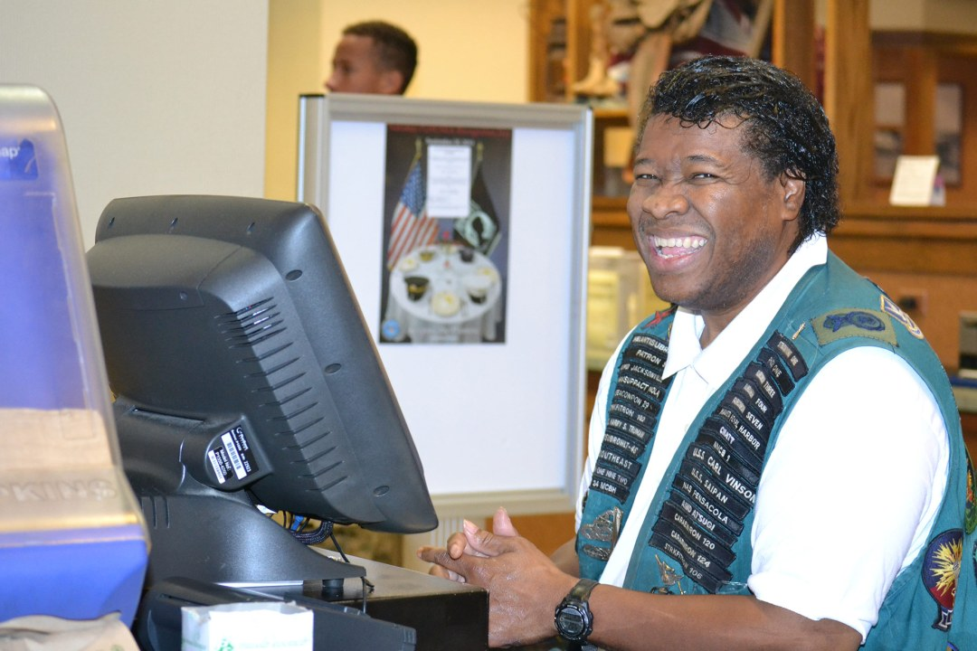 Derek smiles while working the cash register at DRTC's Food Service contract at Tinker Air Force Base.