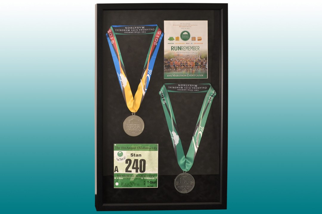Framed medals and racing bib from the OKC Memorial Marathon.