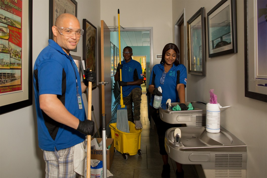 Three DRTC custodians in a hallway holding various cleaning equipment, smiling for a picture.