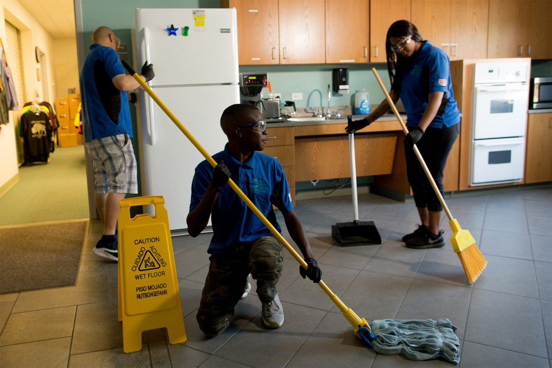 Three DRTC custodians in various phases of cleaning a breakroom kitchen.