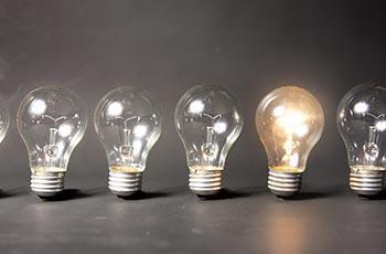 mehrere Glühbirnen eine leuchtet