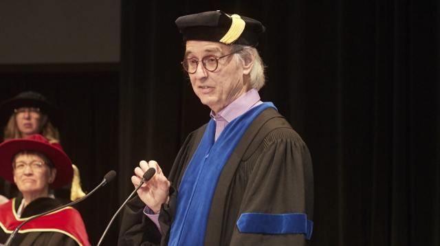 Man giving a speech at commencement ceremony for university students of Adler University
