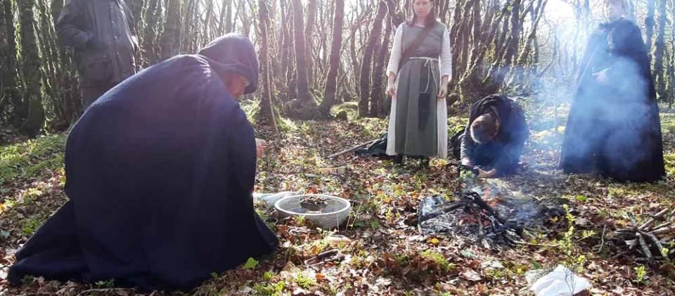 Il y a un barde accroupi devant le feu et l'eau de la déesse Brigantia qui prépare l'instant de bénédiction des talismans. Les rayons du soleil traversant les bois dessinent sur le seul les rayons de l'Awen. Autour du barde les invités et deux sacerdotes en cercle regardent la scène.
