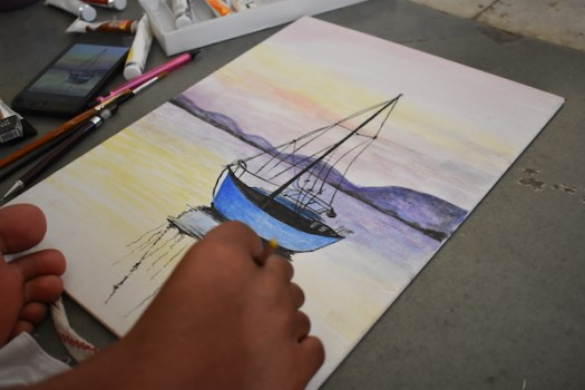 Painting in real time of a sailboat in a body of water. Painter using foot to hold brush.