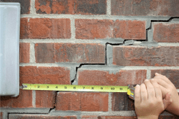 Stairstep crack on brick wall with tape measure