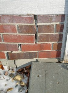stair step crack in brick foundation next to garage door