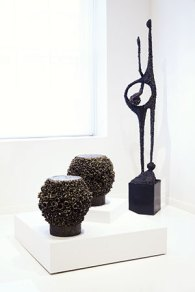 Two styles, one aesthetic: Spore tables bristle with short cuts of pipes of various diameters welded to a base to create an abstract mass, while the 6-foot-tall blackened-steel sculpture Shared Treasure reflects Bearden's interest in the human figure.
