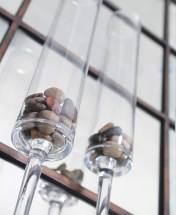 Common items become intriguing with the right presentation. Smooth stones are a study in shapes and subtle colors when displayed in giant flutes.