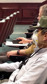 Alec Kala wore a dust mask and sat next to Rock Emmert, a member of Healthy Dubois County, during the Jasper Utility Service Board meeting Monday evening.