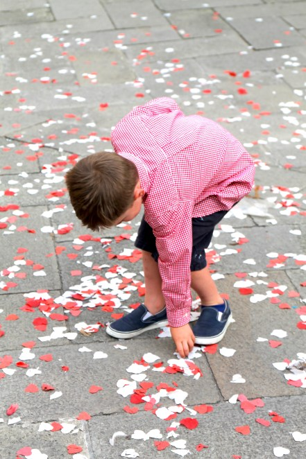 Luc picking up hearts confetti outside one of the many churches after a wedding.