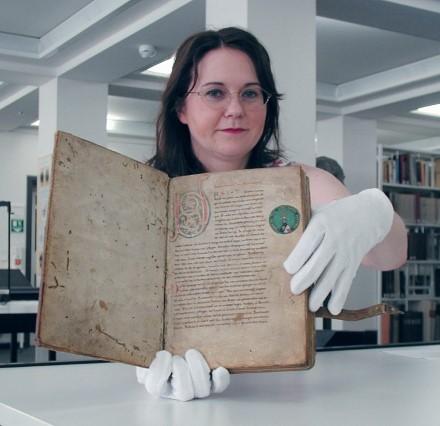Bibliothecaresse toont een van de oeroude handschriften van het Nibelungenlied.