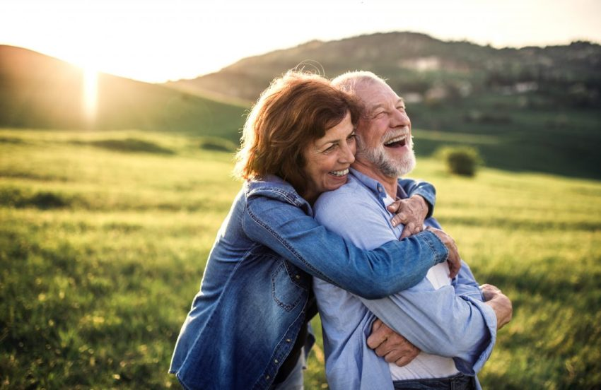 Elderly couple huging and laughing