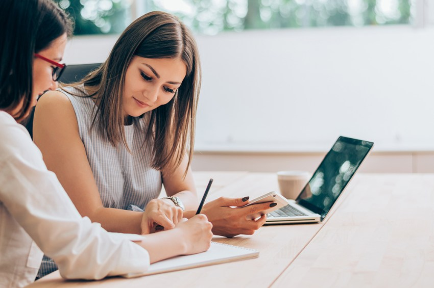 Two women in an office with laptop and notepad
