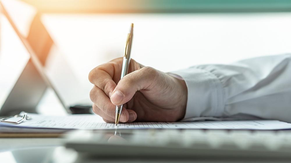 Man writing using clipboard