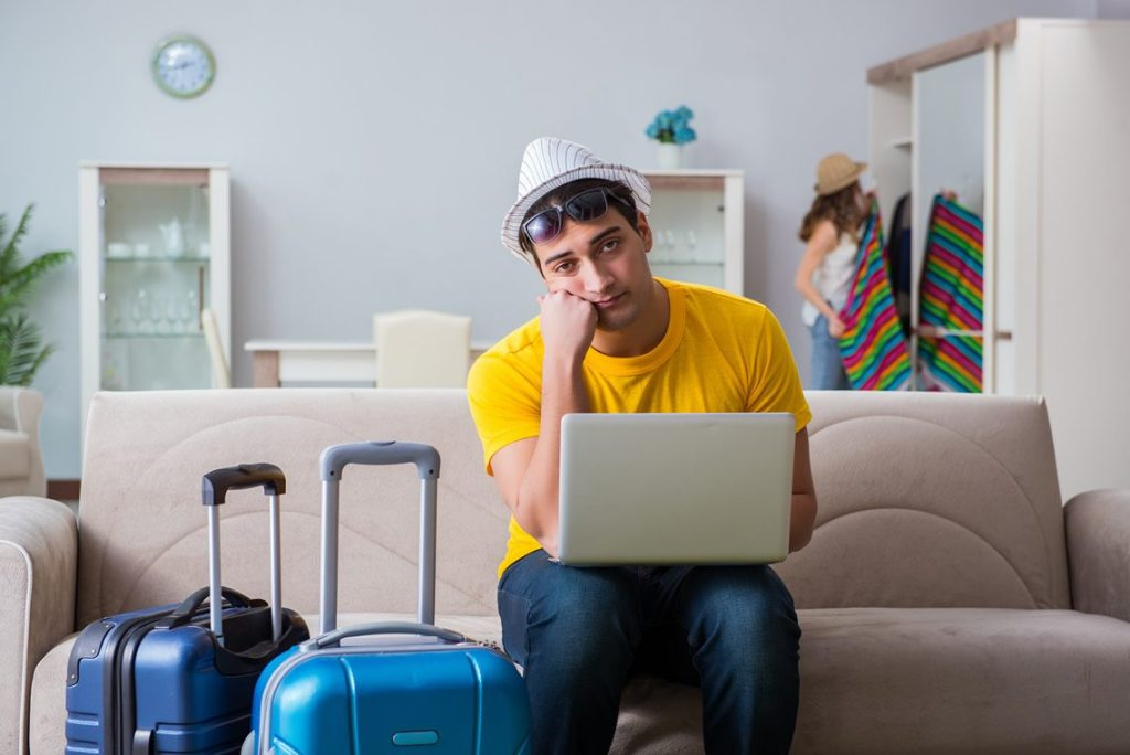 Couple getting ready/packing for a holiday. Man working on laptop.