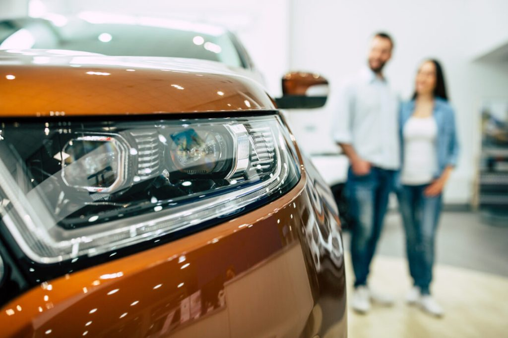 Young couple buying a new car at car dealership, car showroom